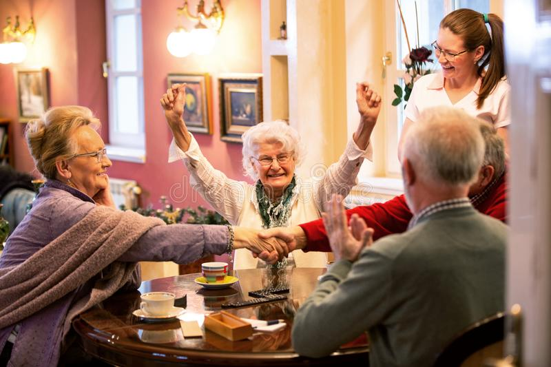 Retirement home occupants sitting at the table together stock photos
