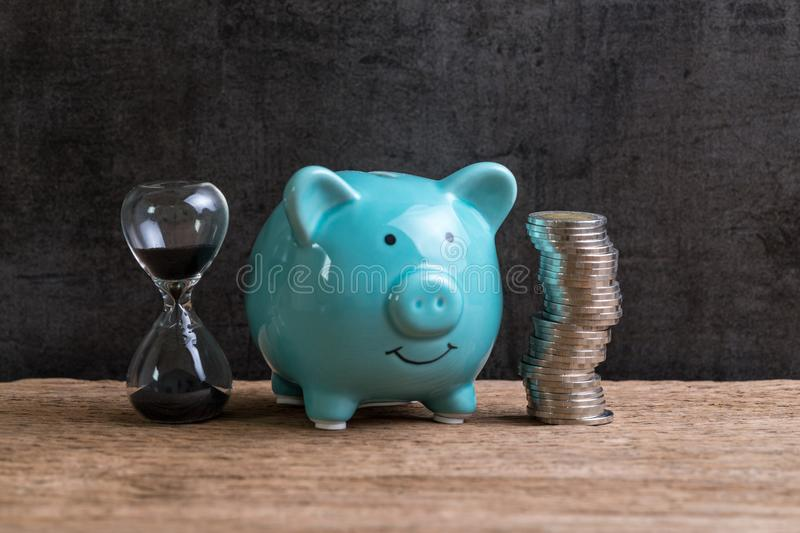 Retirement saving money piggy bank as long term investment concept with stack of coins and sandglass or hourglass on wood table royalty free stock photos