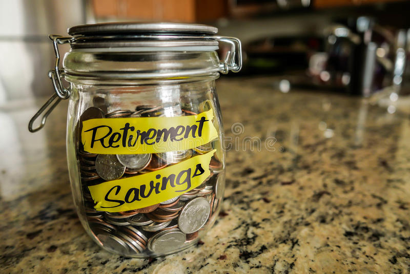 Retirement Savings Money Jar. A clear glass jar filed with coins and bills, saving money. The words Retirement Savings written on the outside stock photography