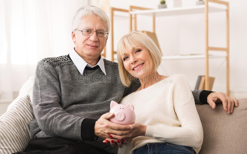 Retirement savings. Senior couple holding piggybank at home. Retirement savings. Senior couple holding piggybank and looking at camera stock photo