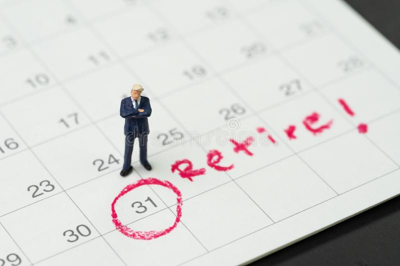 Retirement target or planning to quit job or financial freedom, miniature people businessman standing and thinking about date with royalty free stock photography