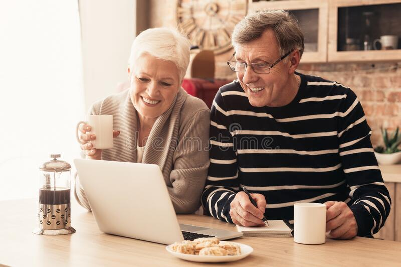 Cheerful senior couple watching news on laptop online at kitchen royalty free stock images