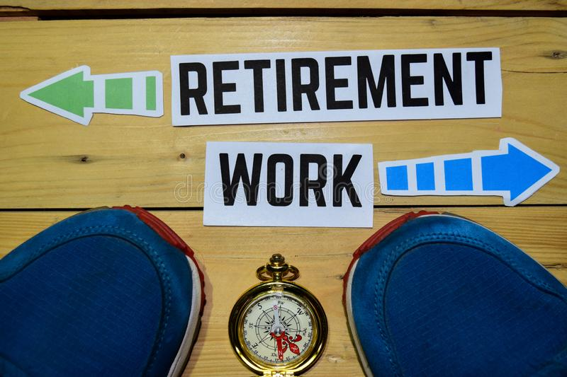 Retirement or Work opposite direction signs with sneakers and compass on wooden. Vintage background. Business, education and finance concepts stock photos