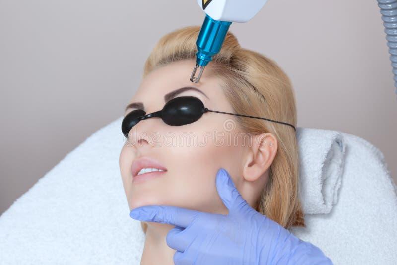 Retiro del tatuaje del laser en las cejas del ` s de la mujer en un salón de belleza fotos de archivo libres de regalías