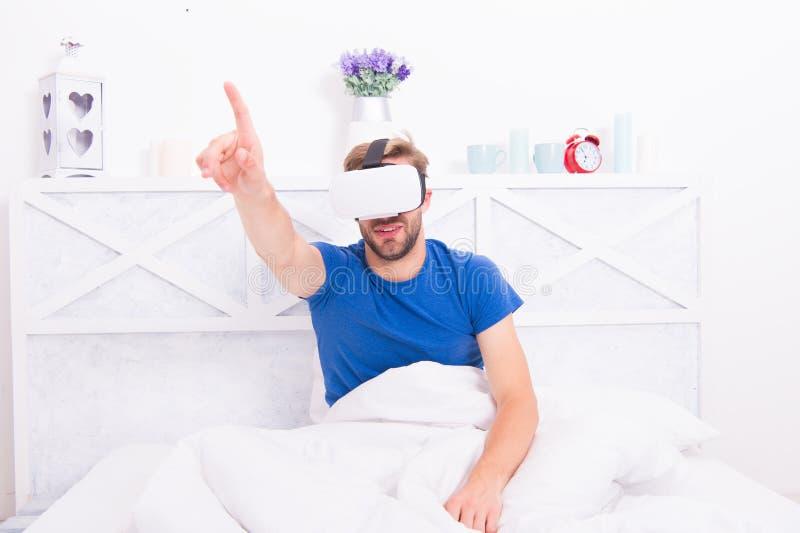 Retorno ? realidade O homem explora o vr ao relaxar na cama Despertar da realidade virtual Tecnologia e futuro de VR imagem de stock