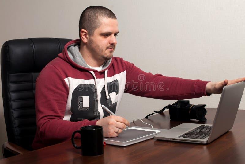 Retoucher работает в офисе стоковые изображения