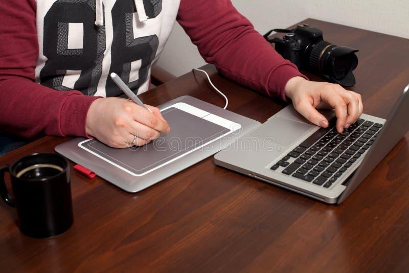 Retoucher lavora al computer portatile fotografie stock libere da diritti