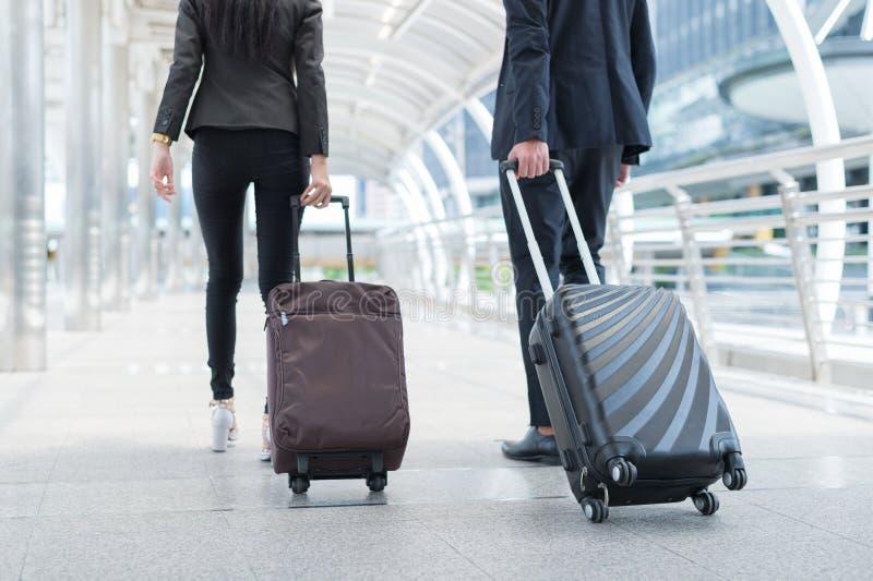 Retour d'un homme d'affaires et d'une femme d'affaires marchent avec bagages dans la rue publique, concept de voyage d'affaires images libres de droits
