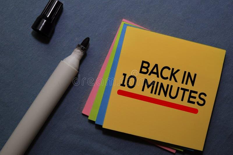 Retour en 10 minutes sur les notes collantes isolées sur le bureau photos stock