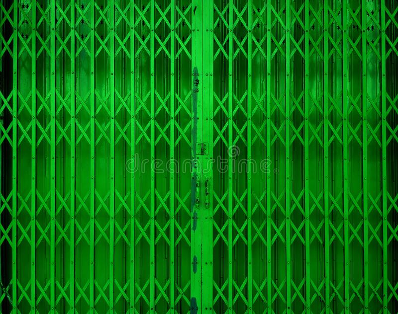 Retractable folding green door gate royalty free stock images