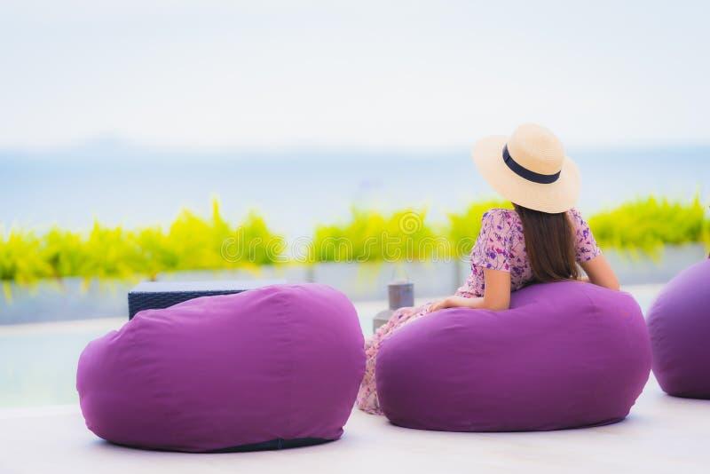 Retrai a linda jovem asiática olhando para o mar com sorriso feliz por relaxar o lazer nas férias fotos de stock royalty free