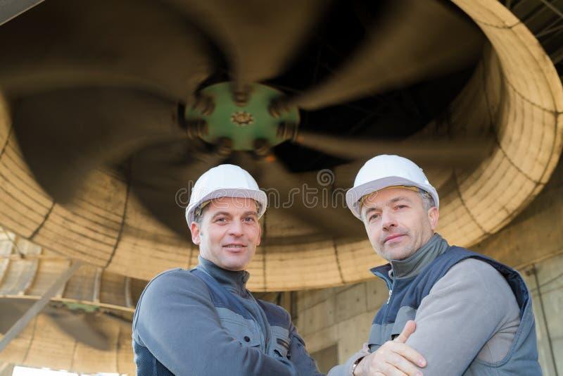 Retrair dois homens sob a turbina industrial fotos de stock royalty free