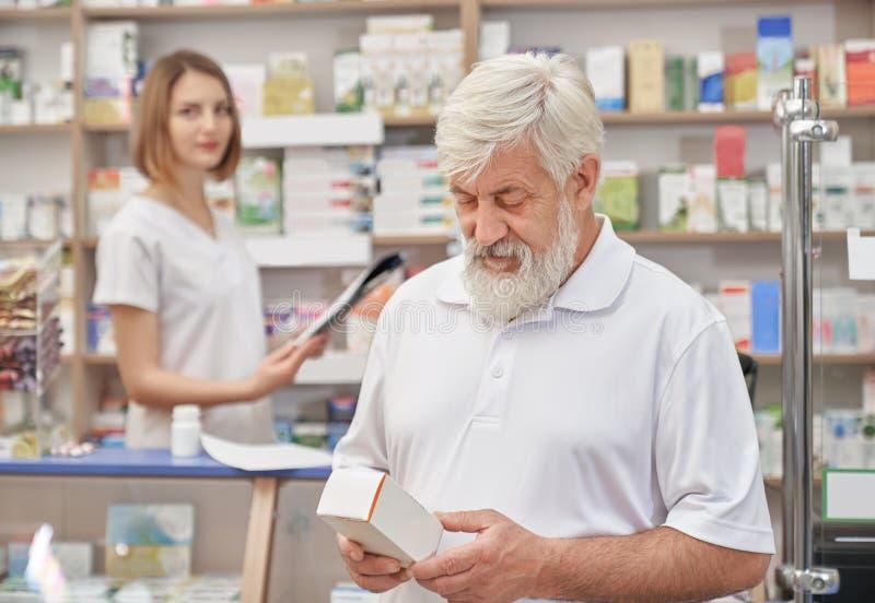 Retraité choisissant le médicament dans la pharmacie image libre de droits