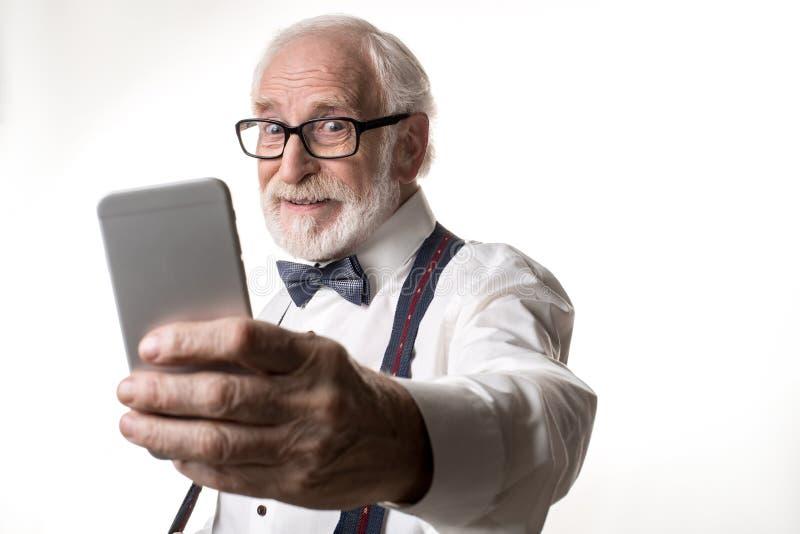 Retraité masculin moderne prenant la photo sur le smartphone image stock