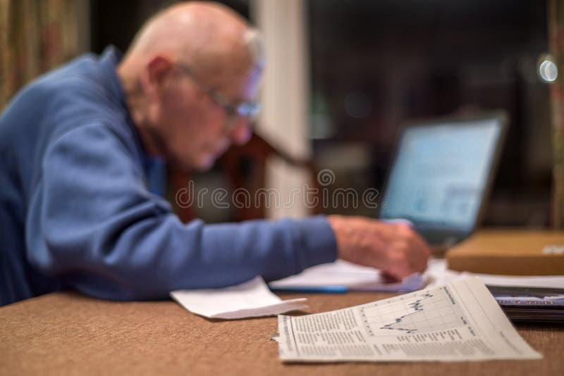 Retraité plus âgé à l'aide d'un ordinateur pour vérifier ses portefeuilles d'actions, Hampshire, Angleterre, U k images libres de droits