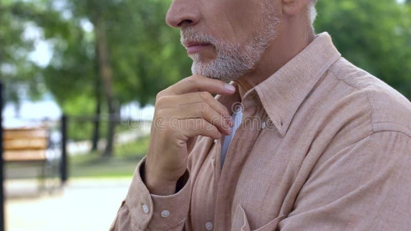 Retraité plus âgé pensant à la décision, touchant la barbe grise, sagesse de vieillesse photographie stock libre de droits