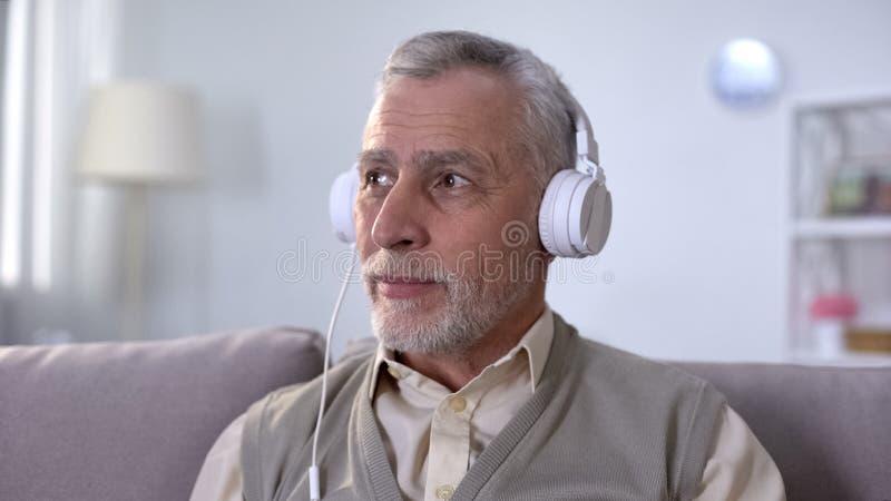 Retraité positif dans des écouteurs écoutant la musique, appréciant la radio préférée images stock