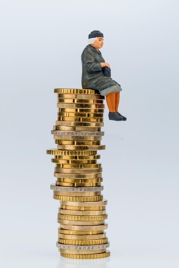 Retraité s'asseyant sur la pile d'argent photographie stock libre de droits