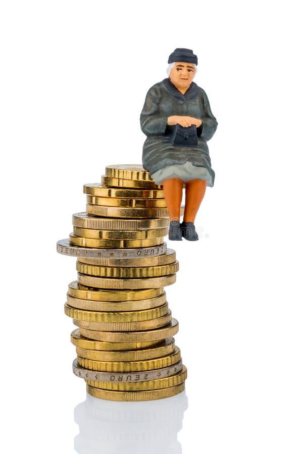 Retraité s'asseyant sur une pile d'argent photo stock