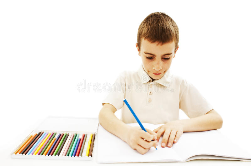 Retrait absorbé de petit garçon avec les crayons colorés photos libres de droits