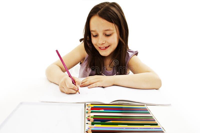 Retrait absorbé de petite fille avec les crayons colorés image libre de droits