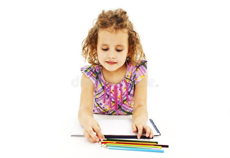 Retrait absorbé de petite fille avec les crayons colorés photo stock