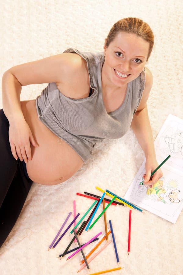 Retrait assez prengnant de femme avec des crayons photo libre de droits