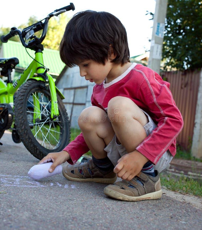 Retrait de garçon avec la craie sur l'asphalte photos libres de droits