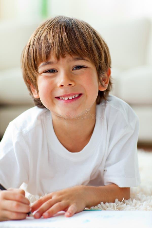 Retrait heureux de petit garçon se trouvant sur l'étage photographie stock libre de droits