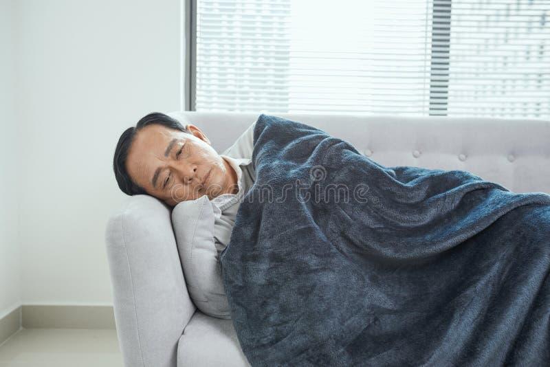 Retrait? masculin dormant sur le divan, souffrant de la haute temp?rature, la maladie images libres de droits