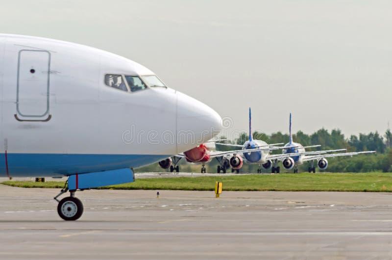 Retrasos y aviones del tráfico de las colas de administración del tráfico antes de la salida En el primero plano la nariz de un a imágenes de archivo libres de regalías