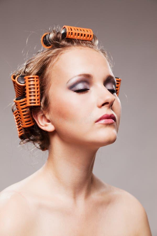 Retrato à moda da menina com composição da fôrma e encrespadores de cabelo, isolador foto de stock