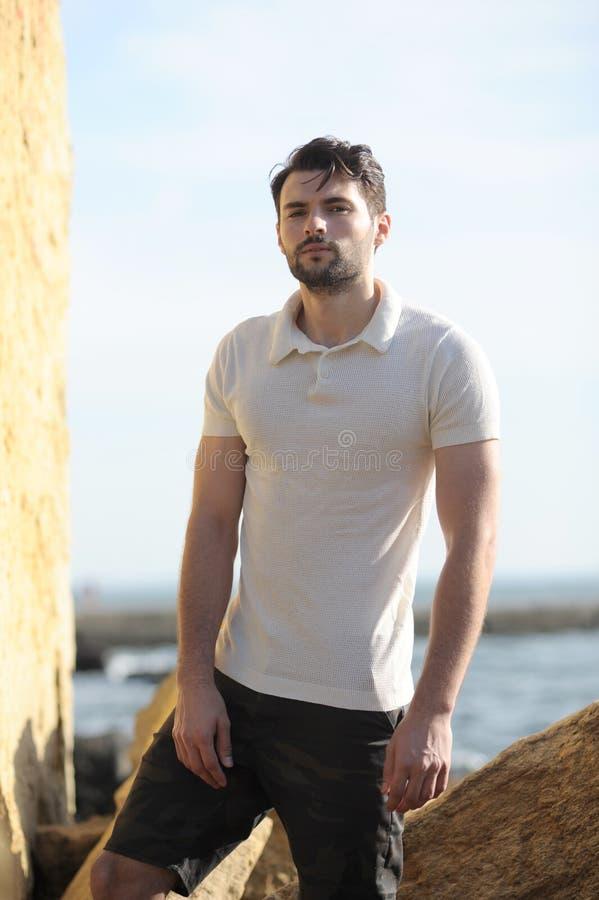 Retrato à moda novo do homem vestido no polo branco e no short preto fotos de stock royalty free