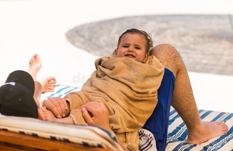 Retrato árabe da menina em suas mãos dos pais fotografia de stock