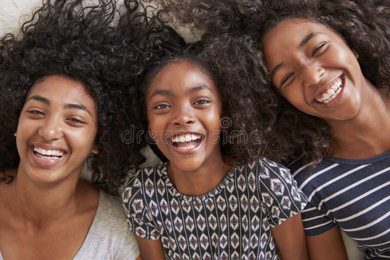 Retrato aéreo de três irmãs adolescentes que encontram-se na cama em casa imagem de stock royalty free