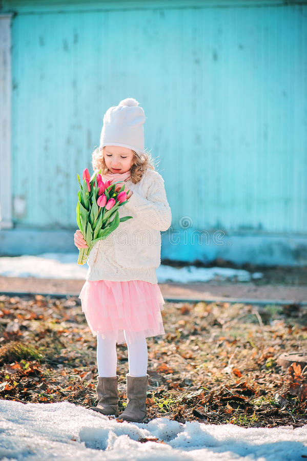Retrato adiantado da mola da menina da criança com as tulipas cor-de-rosa na caminhada imagem de stock royalty free