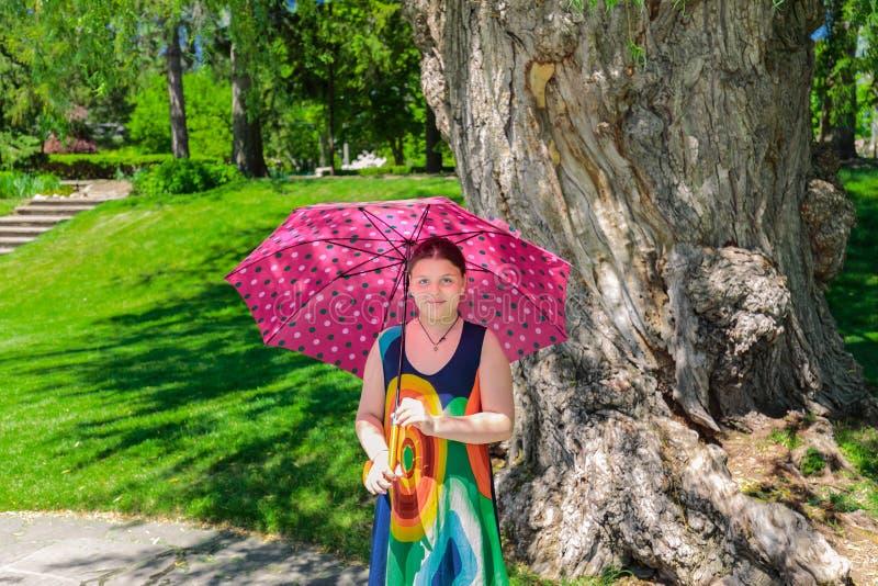 Retrato agradable de una niña elegante con el paraguas que se coloca en jardín el día soleado imagen de archivo