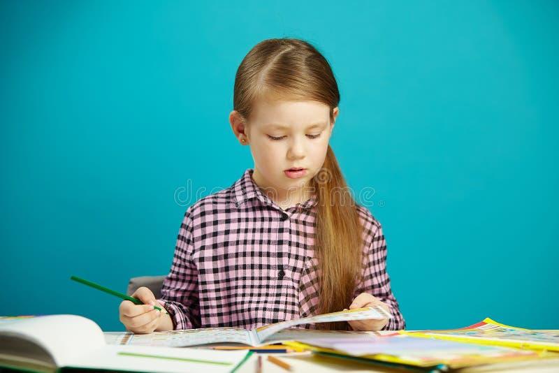 Retrato aislado de la colegiala obediente y diligente que hace la preparación después de escuela El niño disciplinado le gusta ap imagen de archivo libre de regalías