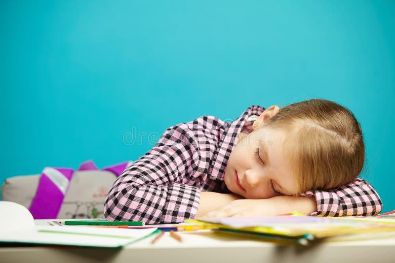 Retrato aislado de la muchacha durmiente dulce en el escritorio durante clase u hometask El niño cansado se cayó dormido en escue fotos de archivo libres de regalías