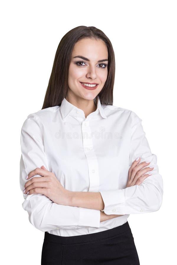 Retrato aislado de una empresaria sonriente que se coloca con sus brazos cruzados y que mira el espectador con confianza foto de archivo
