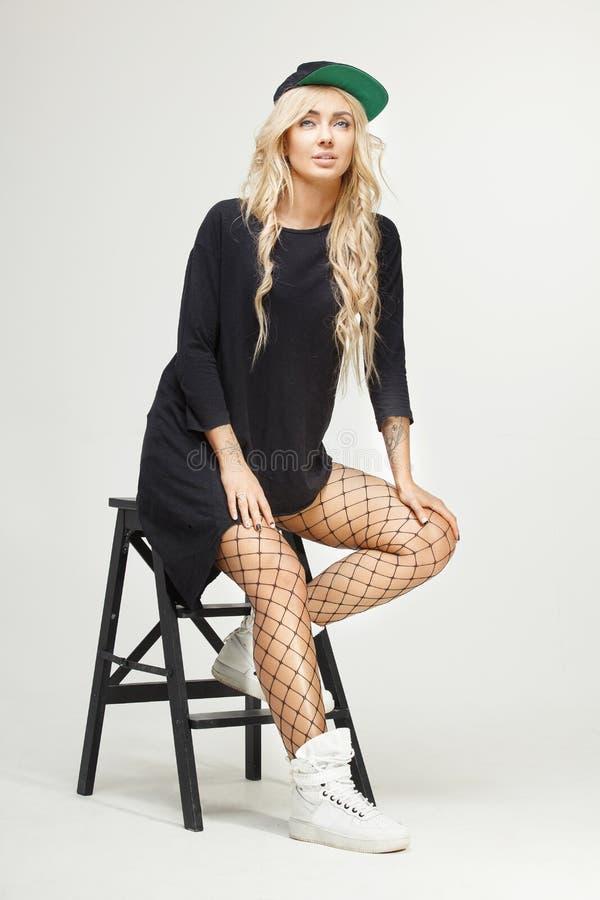 Retrato aislado femenino del swag rubio elegante que se sienta en silla en el fondo blanco moda, tendencias, mirada imágenes de archivo libres de regalías