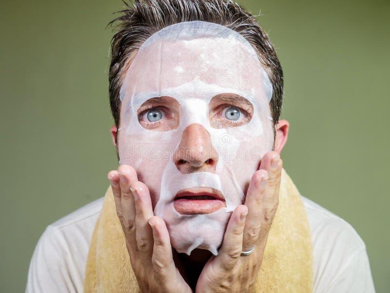 Retrato aislado forma de vida del fondo del hombre extra?o y divertido joven en casa que intenta usando el limpiamiento facial de foto de archivo libre de regalías