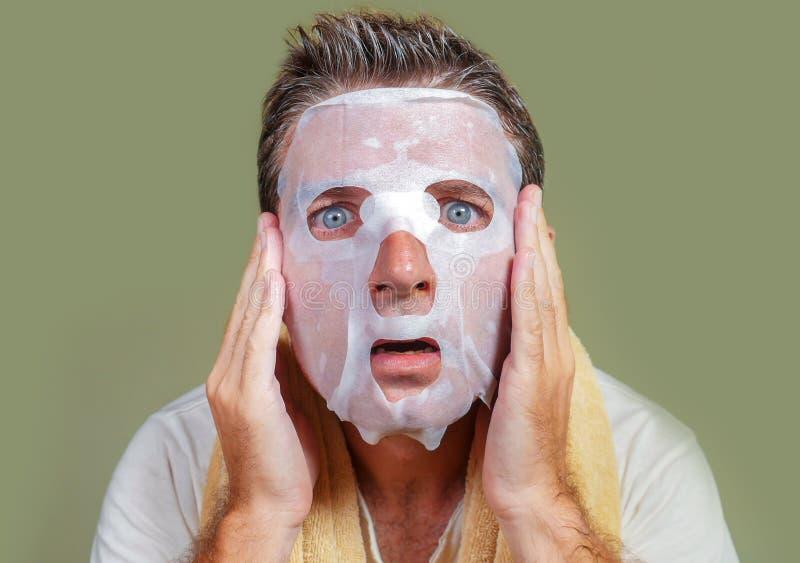 Retrato aislado forma de vida del fondo del hombre extra?o y divertido joven en casa que intenta usando el limpiamiento facial de fotos de archivo