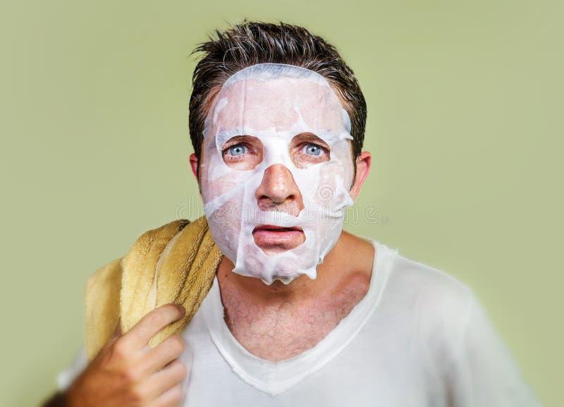Retrato aislado forma de vida del fondo del hombre extra?o y divertido joven en casa que intenta usando el limpiamiento facial de imagenes de archivo