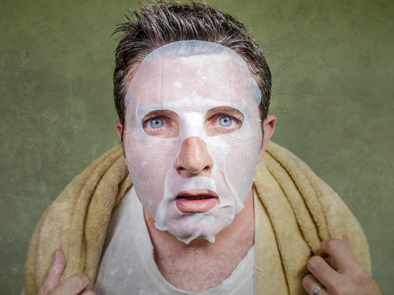 Retrato aislado forma de vida del fondo del hombre extra?o y divertido joven en casa que intenta usando el limpiamiento facial de fotos de archivo libres de regalías