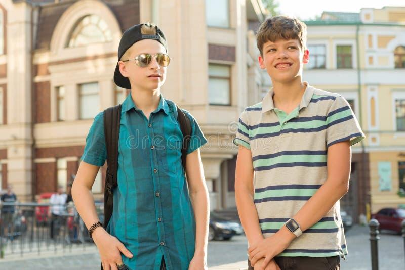 Retrato al aire libre de dos adolescentes 13 de los muchachos de los amigos, de 14 a?os que hablan y que r?en en la calle de la c imagen de archivo libre de regalías