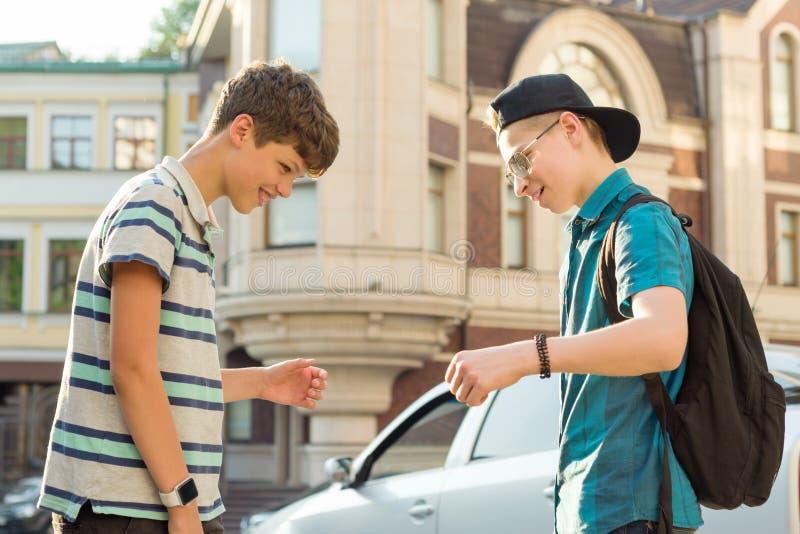 Retrato al aire libre de dos adolescentes 13 de los muchachos de los amigos, de 14 a?os que hablan y que r?en en la calle de la c fotografía de archivo