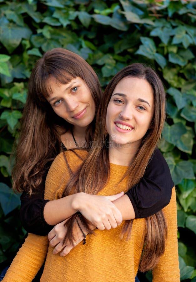 Retrato al aire libre de dos hermanas felices en un parque imágenes de archivo libres de regalías
