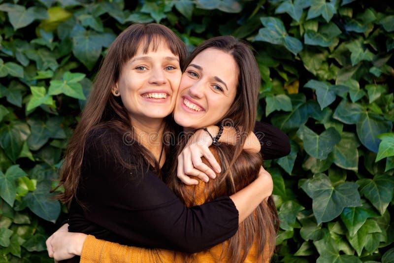 Retrato al aire libre de dos hermanas felices en un parque fotografía de archivo