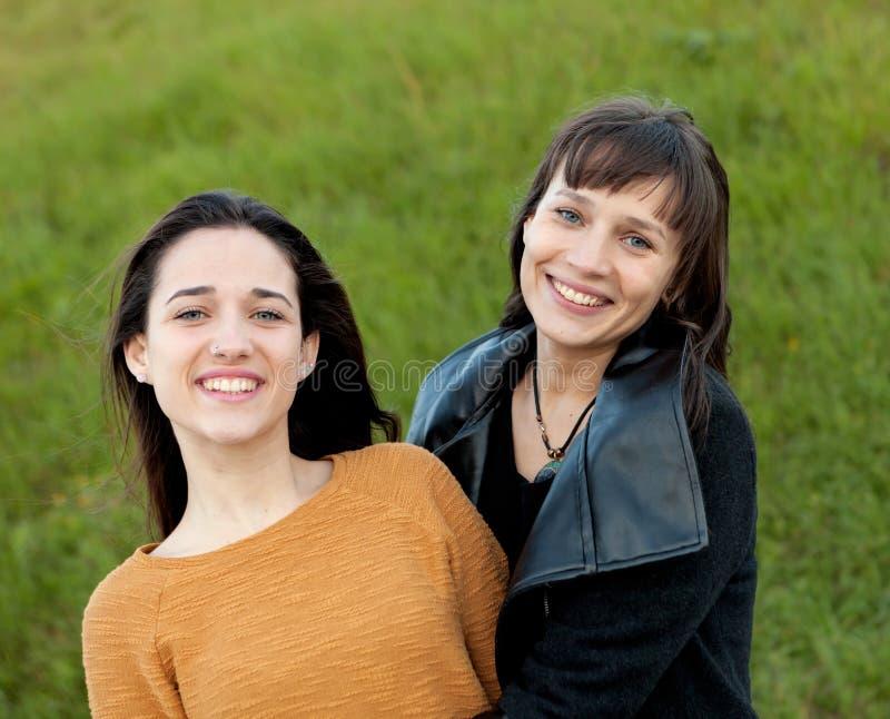 Retrato al aire libre de dos hermanas felices en un parque fotografía de archivo libre de regalías